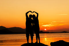 Romance couple making heart shape. With arms sunset background Royalty Free Stock Photos