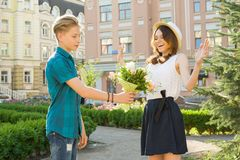 Romance in couple of teens, teenager boy surprises gives bouquet of flowers to his girlfriend outdoors. stock photo