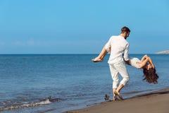 Romance des vacances : couples dans l'amour sur la plage flirtant Image stock