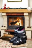 Boots ski boots in front of  fireplace. Romance of downhill skiing. Two ski boots stand in front of a burning fireplace. In the left shoe there is a bottle of stock image
