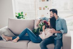 Romance gentle calm atmosphere! Cheerful excited enamored dresse. D in casual jeans clothes husband is hugging his attractive sweet wife with roses on knees Stock Photo