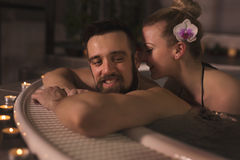 Romance in a jacuzzi bath tub. Couple enjoying and relaxing in a jacuzzi bath with warm water, bubbles and candle light. Focus on the girl Royalty Free Stock Photo