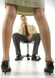 Romance in job. Young, smiling businessman, sitting on chair in front of woman in skirt. White background Royalty Free Stock Images