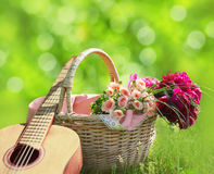 Romance, love, valentine`s day concept - wicker basket with bouquet of flowers, guitar on the grass. Spring fresh sunny background royalty free stock images