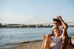 Romance on a river shore. Young hipster couple enjoying the sun Royalty Free Stock Image