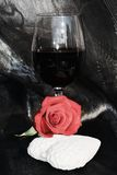Romance, rose and red wine. Love image, close up. Red rose and red wine on sparkling black background. Love and romantic concept, close up Royalty Free Stock Images