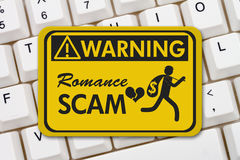 Romance Scam warning sign on a keyboard Stock Photo