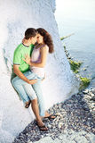 Romance on the seaside. Young couple having romentic minutes on the rocky coast, sunny morning Royalty Free Stock Photography