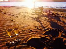 Romance on the shore. Champagne by the glass at sunset on the beach, bike ride and a date Stock Photography