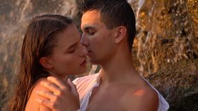 Romance under the waterfall among the rocks during sunset, slow motion. Romance of a young guy and a girl that are going to kiss under the waterfall among the stock footage