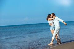 Romance on vacation: couple in love on the beach flirting Stock Photography