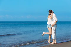 Romance on vacation: couple in love on the beach flirting Stock Images