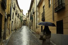 Romancing the Stone. Woman walking up a rain soaked cobblestone street on the way to the castle in Segovia, Spain as a couple pushing a stroller enter the royalty free stock photo