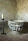 Romanesce baptismal font whit candle in Calatanazor, Soria. Royalty Free Stock Photography