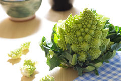 Romanesco broccoli or cauliflower. With florets scattered on a pale wood background and gingham cloth Royalty Free Stock Image