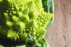 Romanesco Broccoli or Cauliflower on Wooden Table. A romanesco broccoli, also known as a romanesco cauliflower, on a white background. The vegetable's spikes Royalty Free Stock Image