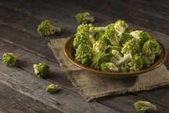 Romanesco broccoli. Plate filled with fresh romanesco broccoli placed on a rustic wooden table. Selective focus Royalty Free Stock Images