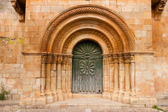 Romanesque portal of Moarves de Ojeda church. Romanesque portal with fine archivolts and beautiful door of the church in a small village called Moarves de Ojeda Stock Images