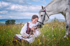 Romania beautiful girl and traditional costume in summer time and beautiful Arabian horse Royalty Free Stock Photography