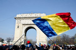 Romania. A big Romanian flag and the Triumph Arc(Arcul de Triumf) with people gather to celebrate Romanias national Day, in Bucharest, 1 December 2013 Royalty Free Stock Photo