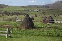 Romania farmland. Haystacks and fences in the romanian countryside stock photo