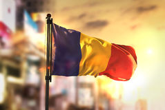 Romania Flag Against City Blurred Background At Sunrise Backligh. T Sky Royalty Free Stock Image