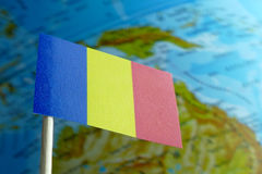Romania flag with a globe map as a background. Macro Stock Image