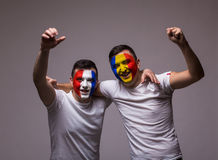 Romania and France national teams celebrate, dance and scream. France vs Romania on white background. Football fans of Romania and France national teams Royalty Free Stock Photography