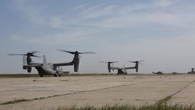 Romania, May 2015, US Marines Two MV 22B Osprey. US Marines. Two MV 22B Osprey aircraft roll over a airfield at a airbase stock video footage