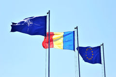 Romania Nato and EU Flags. Romania Nato and European Union flags isolated on blue sky Stock Photos