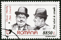 ROMANIA - 1999: shows Oliver Hardy 1892-1957 and Stan Laurel (1890-1965), series Comic Actors. ROMANIA - CIRCA 1999: A stamp printed in Romania shows Oliver stock photos