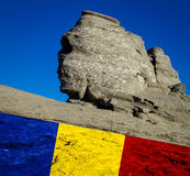 Romania. the sphinx from the Bucegi mountains and the romanian, national flag Stock Photo