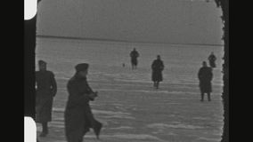 German Soldiers On Frozen Lake. ROMANIA, WINTER 1941. Two Shot Sequence Of A Group Of German Soldiers Taking A Travel Brake Joking And Running On A Frozen Lake stock video
