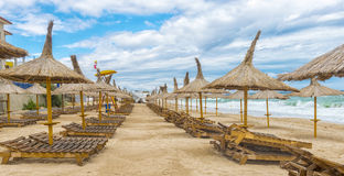 Romanian beach in a windy day, terrace with straw umbrellas Royalty Free Stock Image
