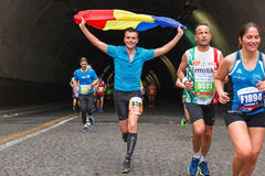 Romanian boy runs marathons and waving Romanian flag. Rome, Italy - April 2nd, 2017: Romanian boy waving flag. Athletes of the 23rd Rome Marathon to the passage Stock Image