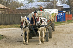 Romanian farmers on road with horse and carriage Royalty Free Stock Photo