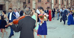 Romanian fiddler greets wedding party leaving Bucharest church Royalty Free Stock Image
