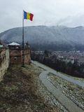 Romanian flag above Brasov city Stock Photography