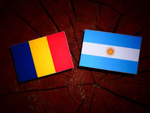 Romanian flag with Argentinian flag on a tree stump isolated Royalty Free Stock Photo