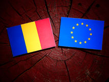 Romanian flag with EU flag on a tree stump isolated. Romanian flag with EU flag on a tree stump Royalty Free Stock Photos