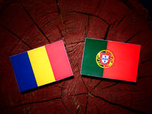 Romanian flag with Portuguese flag on a tree stump isolated. Romanian flag with Portuguese flag on a tree stump royalty free illustration
