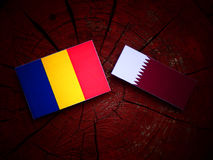 Romanian flag with Qatari flag on a tree stump isolated. Romanian flag with Qatari flag on a tree stump Royalty Free Stock Image