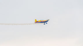 The Romanian Hawks Team pilot with his colored airplane training in the blue sky Stock Images