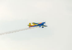 The Romanian Hawks Team pilot with his colored airplane training in the blue sky Royalty Free Stock Photo