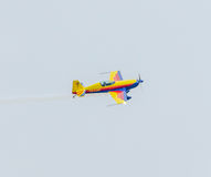 The Romanian Hawks Team pilot with his colored airplane training in the blue sky. Stock Image