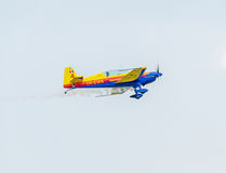 The Romanian Hawks Team pilot with his colored airplane training in the blue sky. Stock Photography