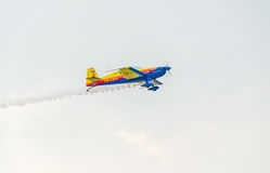 The Romanian Hawks Team pilot with his colored airplane training in the blue sky. Royalty Free Stock Photo