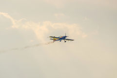 The Romanian Hawks Team pilot with his colored airplane training in the blue sky. Royalty Free Stock Photography