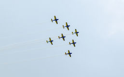 The Romanian Hawks Team pilots with their colored airplanes training in the blue sky. Stock Photography