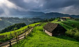 Romanian hillside and village in summer time , mountain landscape of Transylvania in Romania. At sunset royalty free stock images